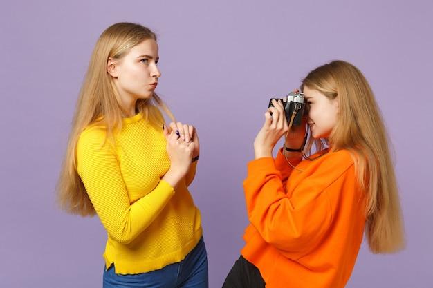 Две очаровательные молодые белокурые девушки сестры-близнецы в красочной одежде фотографируют на ретро-винтажную фотокамеру, изолированную на фиолетово-синей стене. концепция семейного образа жизни людей.