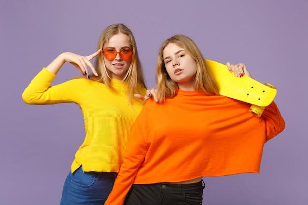 鮮やかな服を着た2人の魅力的な若い金髪の双子の姉妹の女の子、ハートの眼鏡はパステルバイオレットブルーの壁に分離された黄色のスケートボードを保持します。人々の家族のライフスタイルの概念。