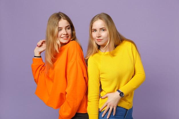 두 매력적인 젊은 금발 쌍둥이 자매 여자 서, 파스텔 바이올렛 파란색 벽에 고립 된 서로보고 생생한 화려한 옷을 입고. 사람들이 가족 라이프 스타일 개념.