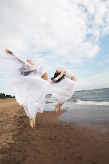 Две очаровательные девушки в белом платье прыгают на берегу моря
