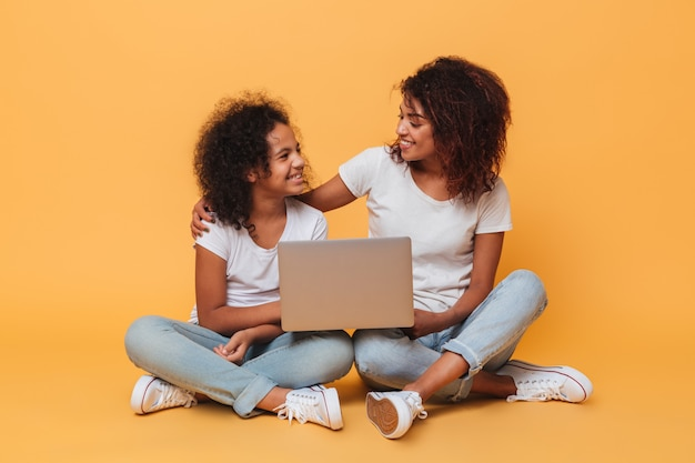 Two cheerful afro american sisters holding laptop computer