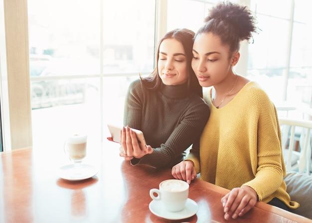 Две веселые и красивые девушки сидят вместе возле стола и что-то смотрят по телефону