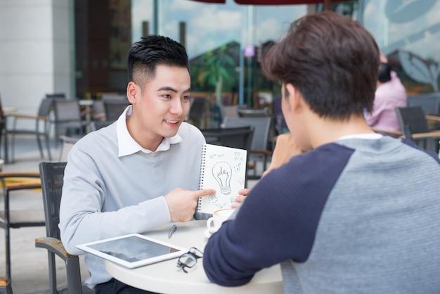 書類について話し合う2人の陽気なアジア人ビジネスマン
