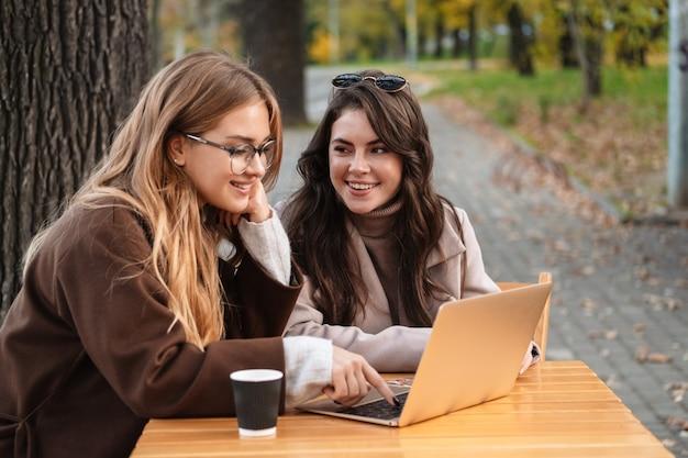 Две веселые привлекательные женщины-друзья сидят в кафе на открытом воздухе и работают над портативным компьютером