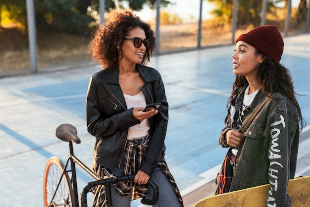 Two cheerful attractive young african girls standing at the sports ground with bicycle and skateboard, using mobile phone