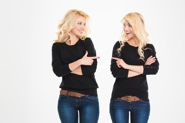 Две веселые привлекательные сестры-близнецы, указывая и глядя друг на друга на белом фоне