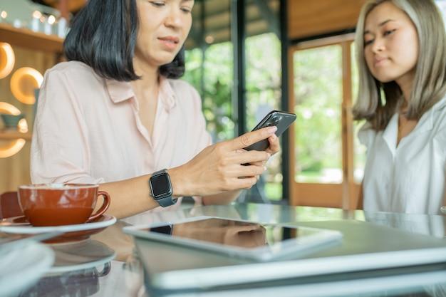 Due ragazze allegre e belle sono sedute insieme vicino al tavolo e guardano qualcosa al telefono. sembrano rilassati e felici. anche le ragazze si stanno godendo il tempo trascorso insieme.
