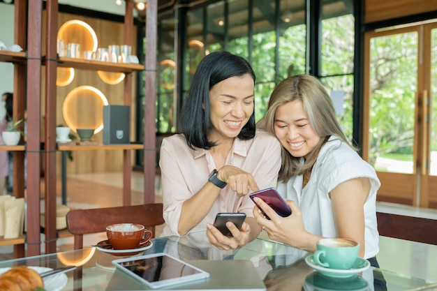Two cheerful and beautiful girls are sitting together near the table and watching something on the phone. they look relaxed and happy. also girls are enjoying the time spending together.