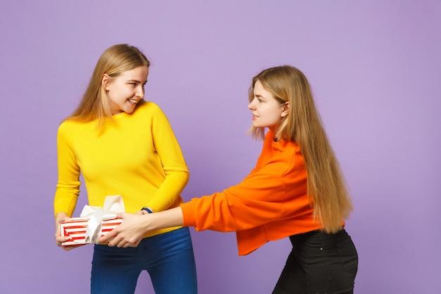 생생한 옷에 두 밝은 금발 쌍둥이 자매 소녀 보라색 파란색 벽에 고립 된 선물 리본이 달린 빨간색 줄무늬 선물 상자를 개최. 사람들이 가족 생일, 휴가 개념.