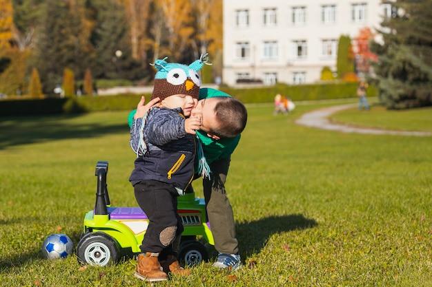 Два веселых брата-мальчика разного возраста развлекаются, играя с большим джипом