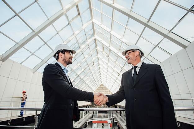 Due uomini d'affari allegri che si stringono la mano nel casco al nuovo edificio