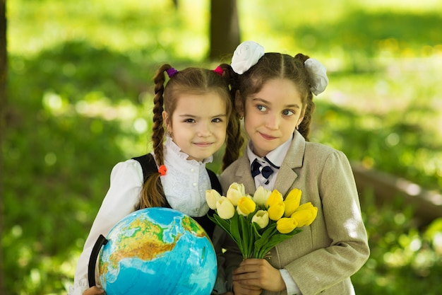 Two cheerful caucasian girls schoolgirls with flowers and a globe