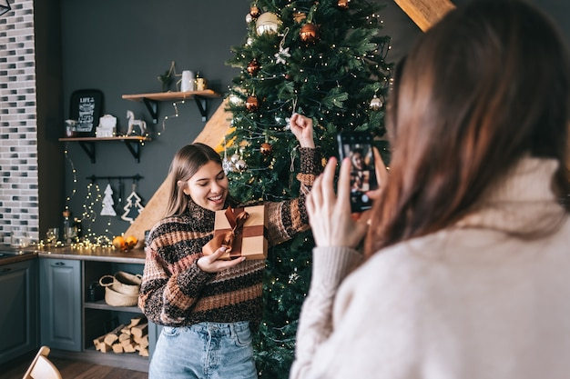 楽しんで、贈り物とクリスマスツリーで写真を作る2人の陽気な白人女性の友人。