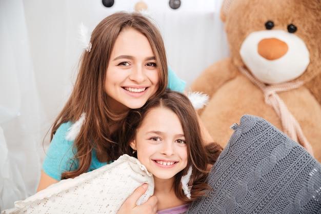 Две веселые очаровательные сестры играют с подушками дома