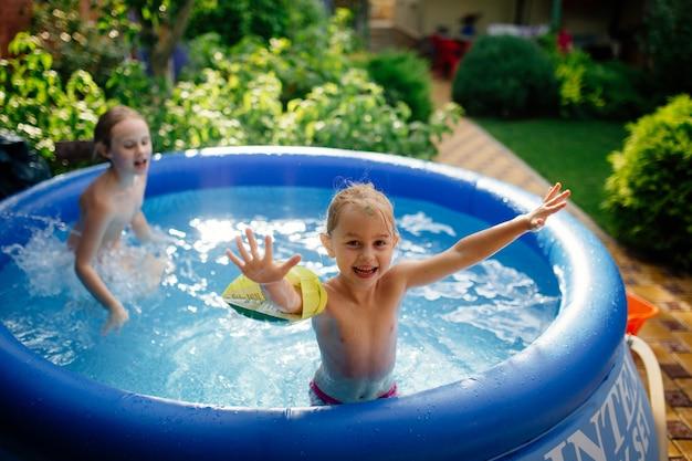 裏庭の膨らませてプールで遊んだり、楽しんだり、水しぶきを上げたり、ジャンプしたりする2人の陽気なかわいい妹。