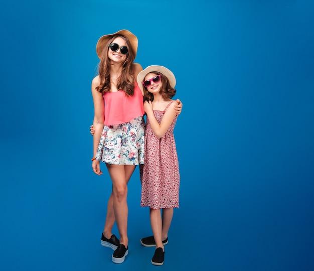 Две веселые милые сестры в солнцезащитных очках и шляпах стоят и веселятся на синем фоне