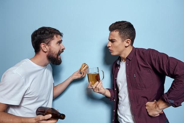 Два веселых пьяных друга пьют пиво и синий фон