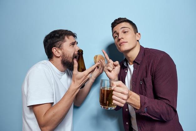 Два веселых пьяных друга пьют на синем фоне.