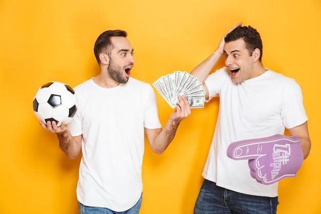 黄色の壁の上に孤立して立っている空白のtシャツを着て、泡の手袋とサッカーで応援し、お金の紙幣を見せて、2人の陽気な興奮した男性の友人