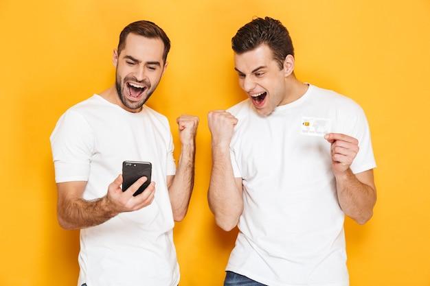 黄色の壁の上に孤立して立って、携帯電話を見て、成功を祝う空白のtシャツを着ている2人の陽気な興奮した男性の友人