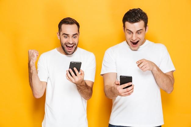 Двое веселых возбужденных друзей-мужчин в пустых футболках стоят изолированно над желтой стеной, разговаривают по мобильным телефонам и празднуют успех