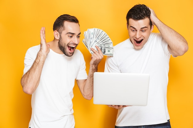 Two cheerful excited men friends wearing blank t-shirts standing isolated over yellow wall, using laptop computer, celebrating success, showing money banknotes