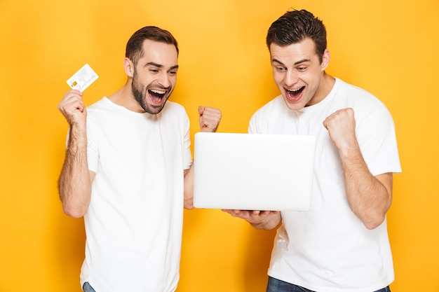 Two cheerful excited men friends wearing blank t-shirts standing isolated over yellow wall, using laptop computer, celebrating success, showing plastic credit card