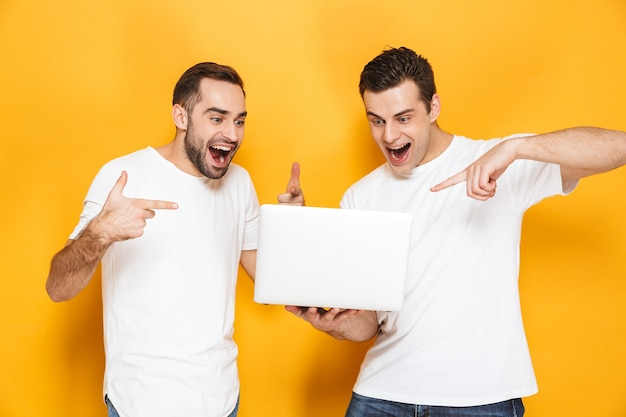 Two cheerful excited men friends wearing blank t-shirts standing isolated over yellow wall, using laptop computer, celebrating success