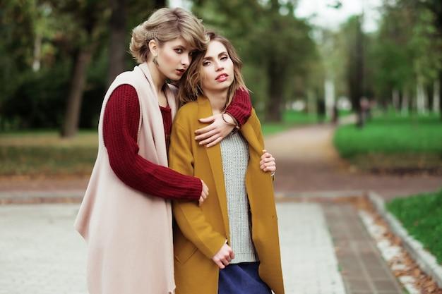 Две веселые модные девушки в осеннем парке