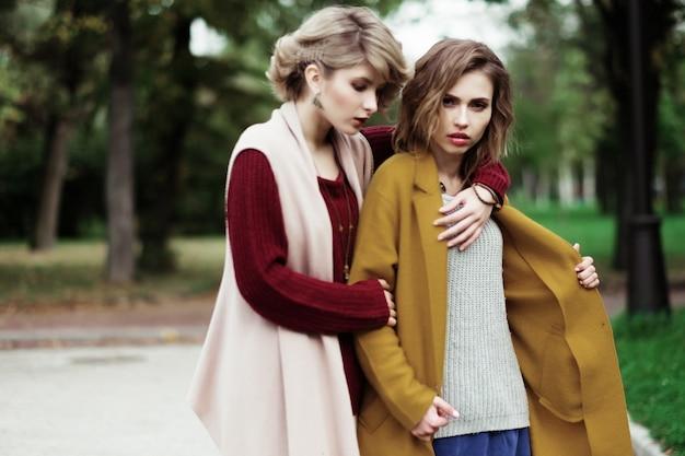 秋の公園で2人の陽気なファッションの女の子