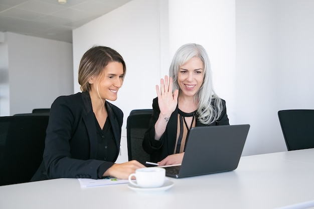 Two cheerful female colleagues using laptop for video call, sitting at table with cup of coffee, looking at display and waving hello. online communication concept