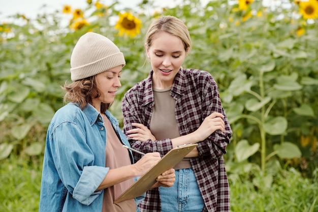 작업복을 입은 두 명의 쾌활한 여성 농부가 카메라 앞에서 해바라기 밭을 바라보는 동안 그들 중 한 명이 토론 중에 메모를 하고 있습니다