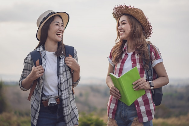 Two cheerful female traveller in countryside