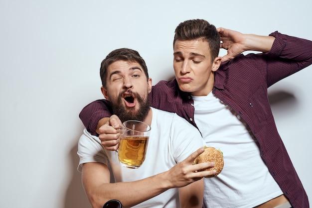 Два веселых друга пьют пиво и веселятся на светлом фоне.