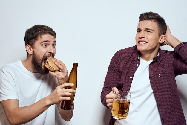 Два веселых друга пьют пиво на светлом фоне.