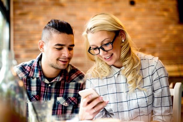 Две веселые друзья хорошо проводят время в кафе, выглядят счастливыми