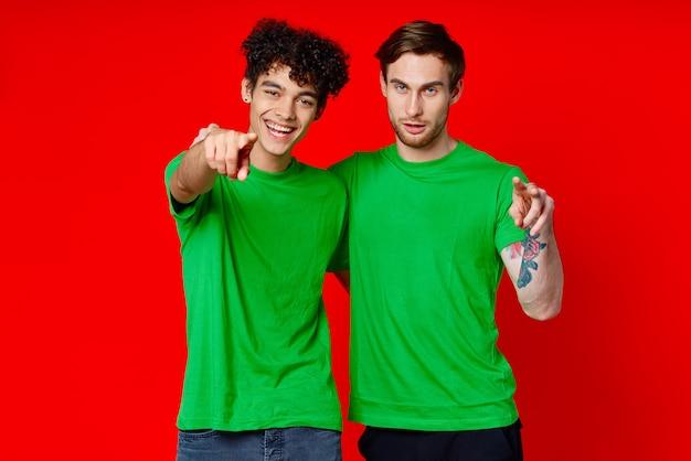 2人の陽気な友人が緑のtシャツの感情を抱きしめます