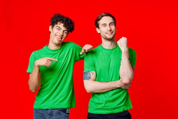 緑の t シャツを着た 2 人の陽気な友達が隣に立っている