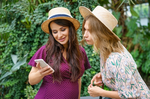 Two cheerful friends look at the phone, make selfie hats on a green background natural.