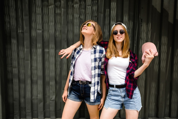 Two cheerful funny girl wearing checkered shirts posing against street wall at the street.