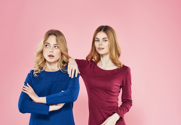 Two cheerful girlfriends in dress glamor studio fashion friendship pink background