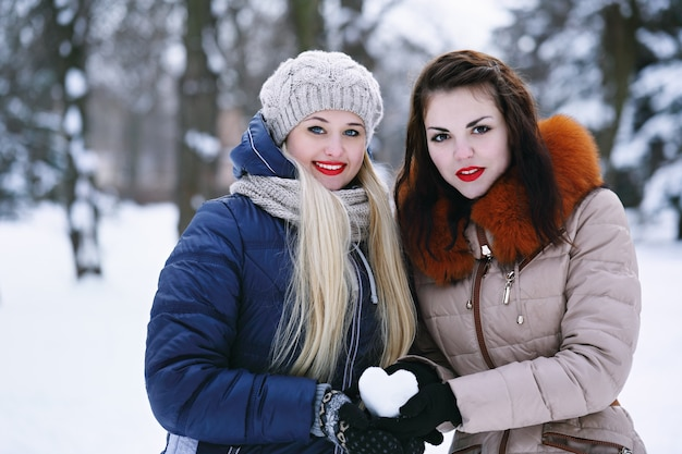 Two cheerful girlfriends holding a snowy heart