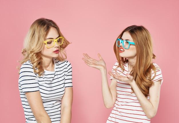 Две веселые подружки в полосатых футболках стоят бок о бок на розовом фоне