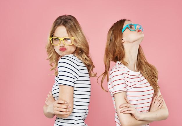 Две веселые подружки в полосатых футболках стоят бок о бок на