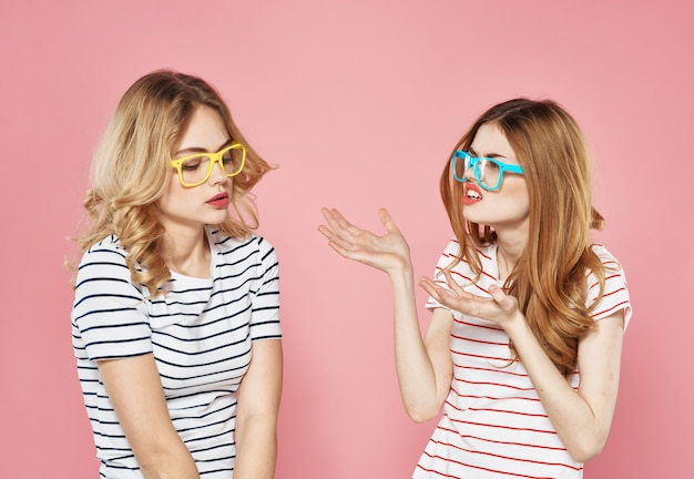 Two cheerful girlfriends in striped t-shirts are standing side by side on a pink background