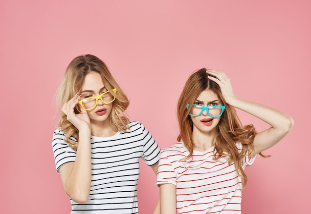 Two cheerful girlfriends in striped tshirts are standing side by side on a pink background