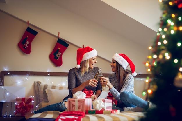 Две веселые подруги в шляпе санты сидят на кровати на рождество и приветствуют пивом