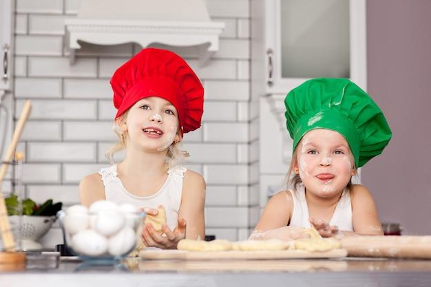 色のキャップで調理する2人の陽気な女の子が生地を準備します。