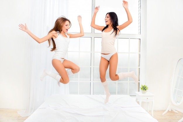 Две веселые девушки в пижамах танцуют на кровати и смеются
