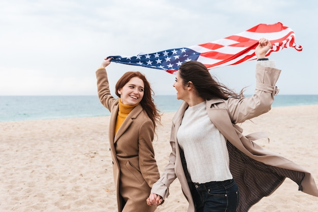 アメリカの国旗を運ぶビーチで走っている2人の陽気な女の子